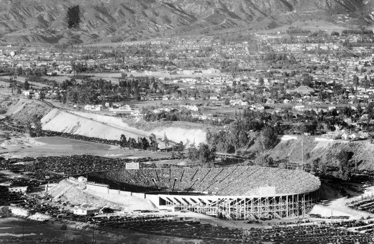(ca. 1928)^ - Aerial view of the Rose Bowl after the southern stands were constructed making it a complete bowl. Though the stadium appears to be filled to capacity, people are still trickling in, and row upon row of automobiles can be seen neatly parked in the lots. View also shows the residential homes surrounding the stadium, as well as the mountains in the background.
