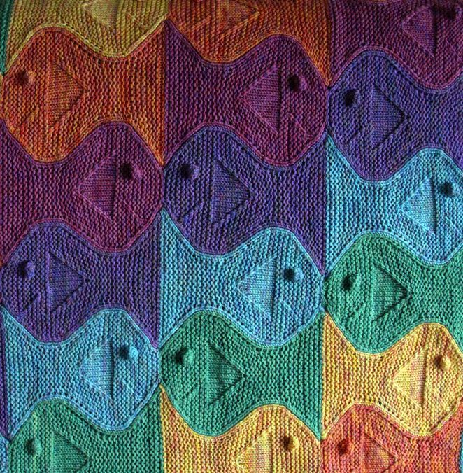 Knitting Pattern for Festive Fish Baby Blanket - This modular afghan of tessalated fish is a great stash buster and portable project. Designed by Paula Levy. Available in Babies and Toddlers: A Knitter's Dozen. Pictured project by devittles