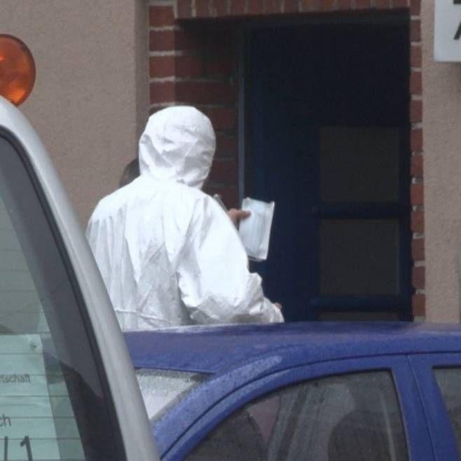 Ein Kriminalbeamter vor dem Haus, wo das Verbrechen geschah. Spuren werden gesichert