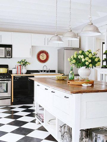 white kitchen island with butcher block wood top and storage for dishes on bottom, black and white checked floors, black dishwasher, farmhouse sink, metal hanging industrial lights, pops of red and green and yellow