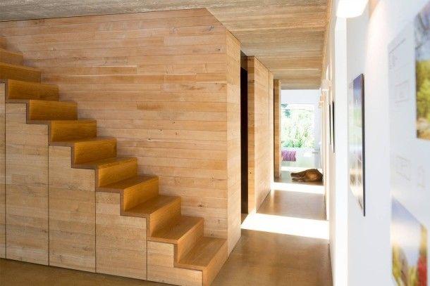 Gestern Futtergang, heute Flur: Die Planer haben sich an der ursprünglichen Struktur des Stalls orientiert. Statt Wände einzuziehen, um Zimmer zu schaffen, haben sie den Holzblock ins Zentrum gesetzt. Er birgt Gästebad und einen Büroraum, zum Wohnbereich hin die Küche. Die Treppe führt hinauf auf die Galerie, wo die Architekten ihren Arbeitsplatz haben.