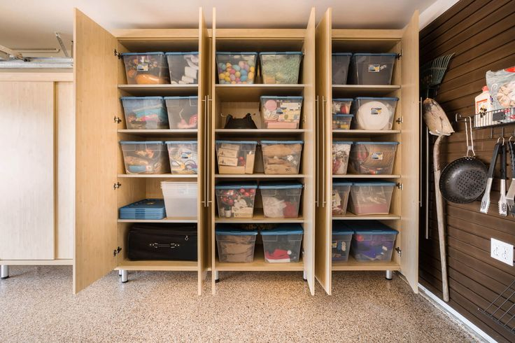 Large maple melamine cabinets contain large storage bins doubling the garage's storage space. The combination achieves a well-organized clean look for a workspace.