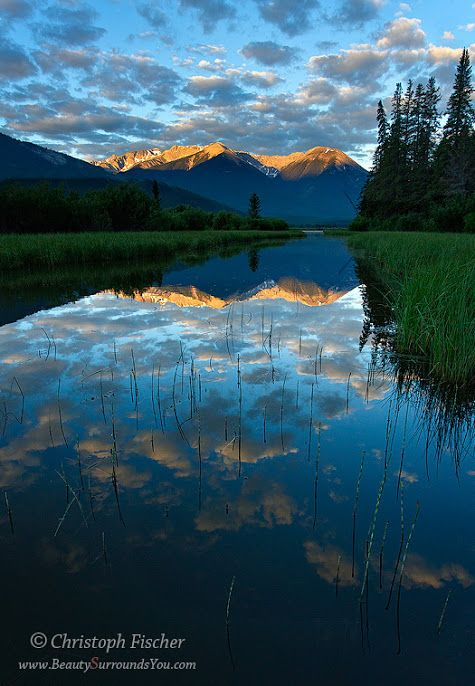 Photo by Christoph Fischer  Beautiful puffy clouds reflect in the calm waters of Vermillion Lakes in the Canadian Rockies, while the distant mountains catch the first rays of the morning sun.Photo