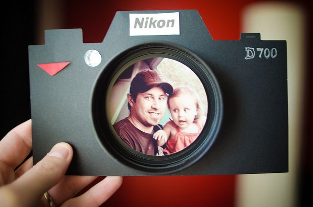 Camera Father's Day card - O.k. so I saw this idea in Family Fun magazine and I knew it would be the perfect father's day card. I cut out the shape of a camera (I have a cricut machine that did it) then I spray painted a peanut butter lid black for the lens. I used a silver pen for the D700, a rhine stone for the AF assist, and I just cut out the Nikon from a magazine ad.