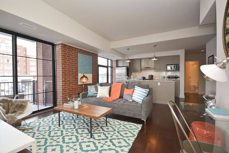 We loved mixing both colour, styles and textures in this space - the aqua, the tangerine, the prints and graphics and the wood, brick and glass all work together to create a perfect balance in this condo space