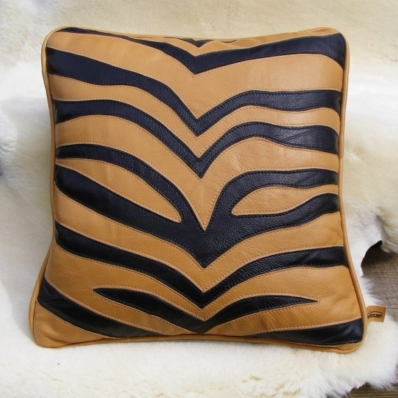 "*Africa comes alive in your house with this life-size leather stripe    * predominantly gold stripe and black with black faux fur back    * 16"" with gold leather welt and zipper close. $90"