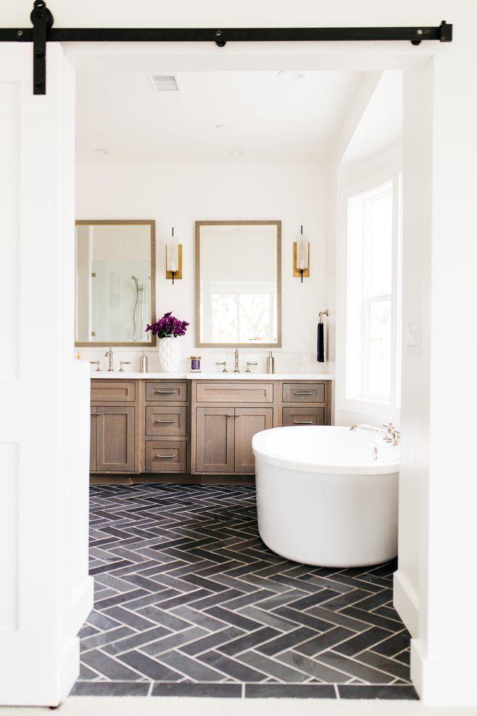 @greigedesign free standing tub, sliding door, gold mirrors, vanity, floor
