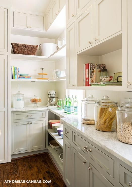Two tone kitchen pantry features white upper cabinets and gray lower cabinets topped with white marble countertops. An open cookbook shelf stands over glass canisters filled with goodies. Long butler's pantry boasts open shelving placed under a window next to stacked wraparound shelves.