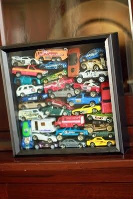 Put your son's toy cars in a shadowbox after he has outgrown them and use to decorate his room.