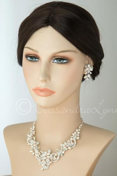 This carefully hand-wired bridal necklace set features rhinestone covered swirls or scrolls and ivory freshwater pearl. IT is a beautiful design sure to be a w