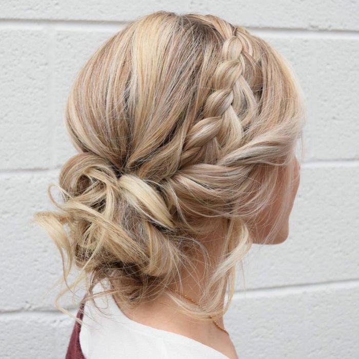 Coiffure demoiselle d'honneur flou cheveux blonds, tresses et petits pains sur les cheveux