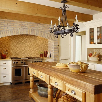 love this tudor style kitchen. open ceiling beams, block island, arch over range.