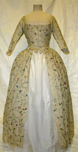 A woman's gown of linen tamboured in an all-over pattern of serpentine trails with flowers and leaves in shades of pink, green, yellow and red, with additional herringbone stitch. 1770s (embroidery) 1780s (sewing) 18701890 (altered) | V&A Search the Collections