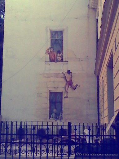 Funny scene painted on to the wall of an old building near the Romanian Athenaeum (Romanian: Ateneul Român), in Bucharest.