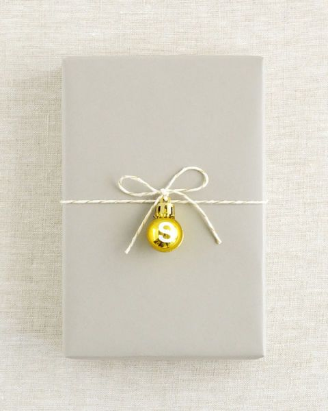 This technique is an easy way to keep gift wrapping clean and classy this holiday season. To personalize your gift tag, add a small letter sticker to the ball ornament.