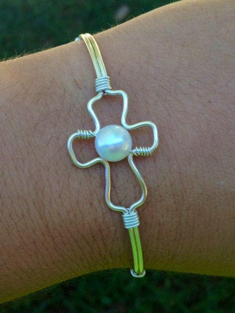 pulsera brazalete en forma de cruz, hecha con alambre.