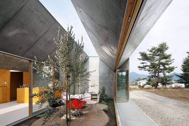 Completamente aperta, la sala da pranzo si trasforma in un piccolo giardino, con tanto di piante, prato e amaca. Sedie Eames Plastic Side Chair; tavolo Dining Table, design Isamu Noguchi. Tutto di VIT