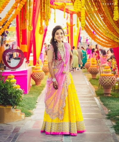 Mehendi Outfits - Yellow Lehenga with Pink Detailing | | Yellow Light Lehenga with Pink Choli and Net Pink Dupatta, Floral Jewelry Mehndi function ideas