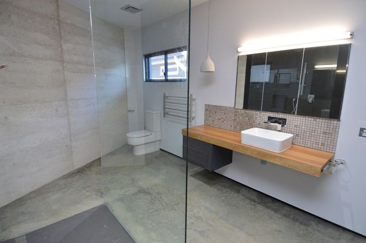 At the forefront of interior design trends - this bathroom has been inspired by shows like the block with its use of frameless panel, concrete and wood for a warm industrial effect.