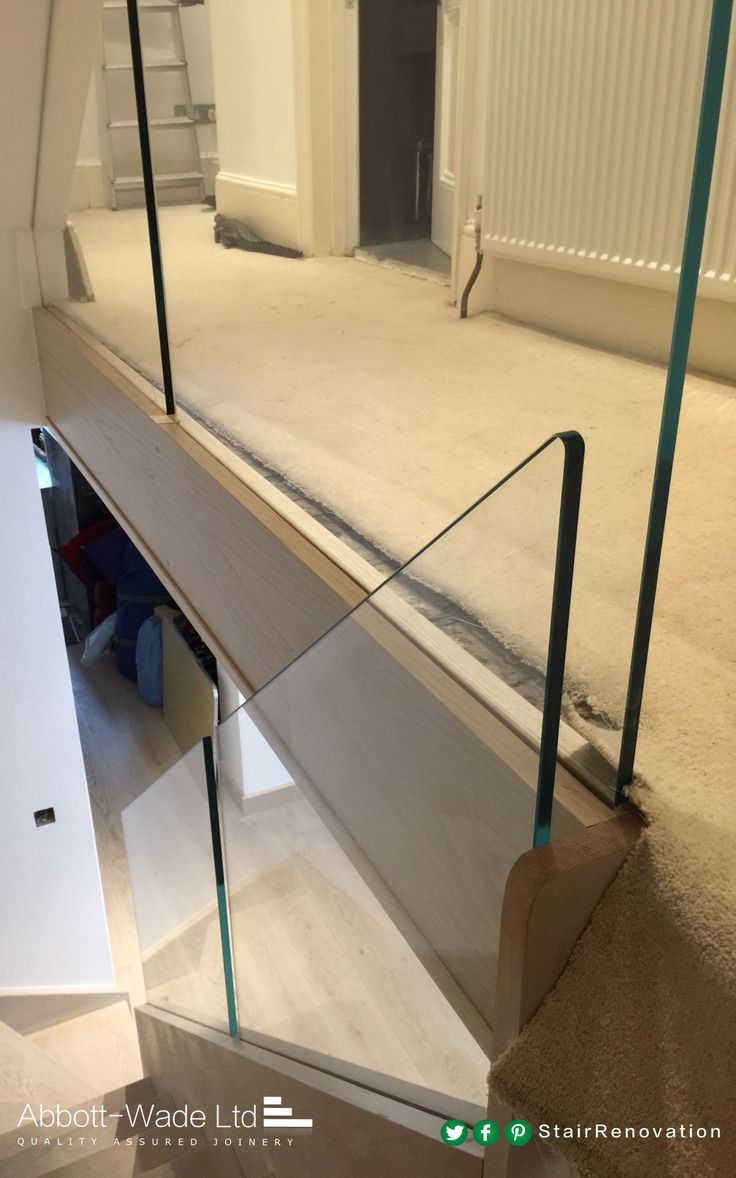 Stained oak staircase with frameless glass balustrade waiting for new carpet.
