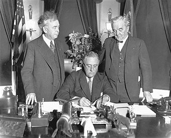Franklin Delano Roosevelt, with Congressman John Rankin of Mississippi (left) and Senator George Norris of Nebraska, signs the Norris-Rankin Power bill, which provided for the creation of the Tennessee Valley Authority, April 14, 1933.