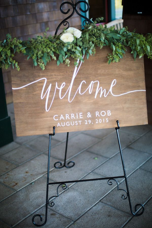 A gorgeous calligraphed sign was decorated with fresh greenery at the reception entrance.  Reception Venue:Black Rock Country Club  Floral Designer:Beach Plum Floral Design