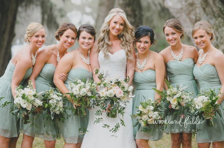 the bride and her bridesmaids show off their bouquets. bride carries bouquet  of kiera garden roses, light pink ranunculus, white ranunculus, white veronica, white anemone, patience garden roses, cafe au lait dahlia, jasmine trails, dusty miller, fern & greenery wrapped in green gingham check ribbon and the bridesmaid carries a bouquet of vendela roses, white stock, white lisianthus, white queen anne's lace, seeded eucalyptus, dusty miller, fern, jasmine trails, white fountain grass…