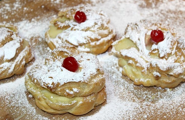 Saint Joseph's Day zeppole recipe. Cream puff shells filled with a vanilla custard cream, dusted with confectioners' sugar, and topped with cherries.