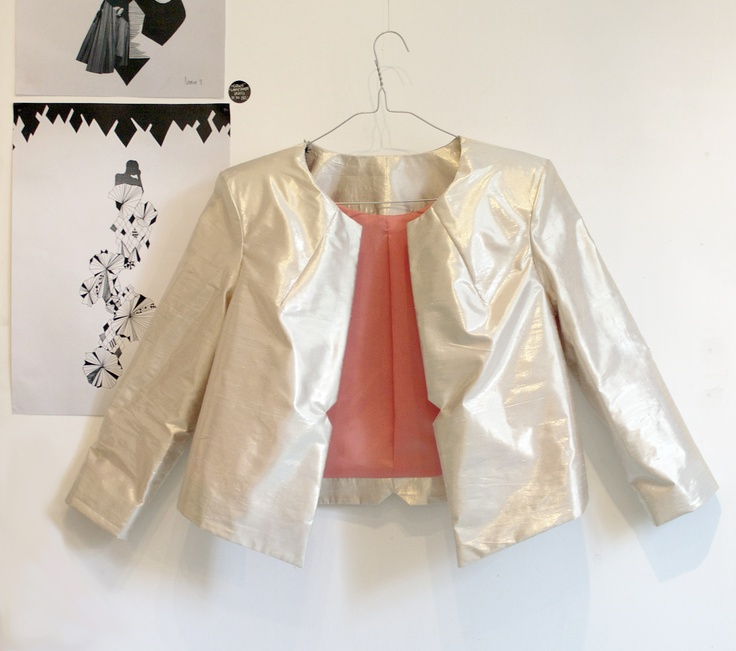 Golden jacket by Tibbe Smith. Illustrations by Charlotte Cederkof in the background. Designkollektivet.dk