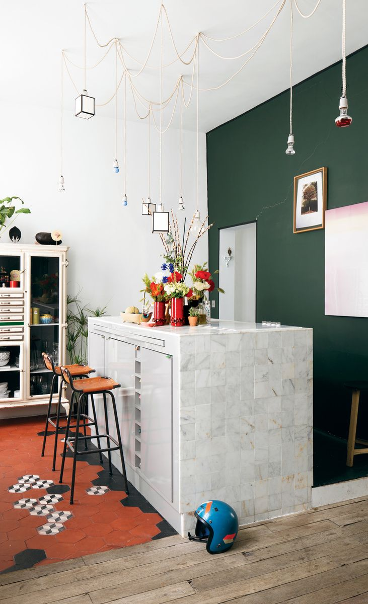 Aumas designed the kitchen island, which is covered in marble tiles from Carrelages du Marais—the geometric floor tiles are from the same place—and strung the matrix of lights up above it. The barstools by Charlotte Perriand were discovered in a vintage store in Antwerp, Belgium. The green wall is covered in paint from Emery & Cie. Photo by: Christian Schaulin