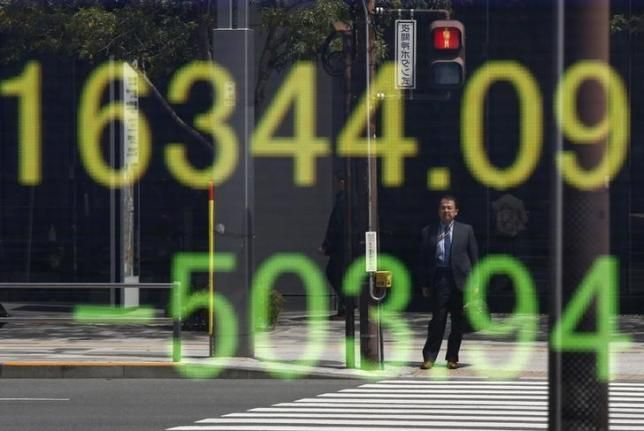 A businessman is reflected in an electronic board displaying Japan's Nikkei share average outside a brokerage in Tokyo, Japan, April 18, 2016.  REUTERS/Toru Hanai