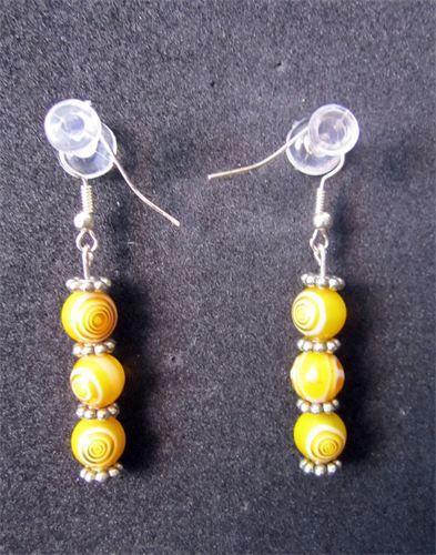 Spiral - 11    Mellanlånga örhängen med detaljer i silverpläterad metall. Tre runda glaspärlor i Gul/Vit Spiralmönster på rad, samt nickelfria krokar. Frakten är inkluderad i priset.    Pris:  110 kr