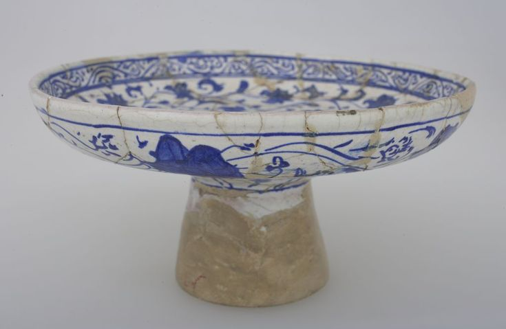 Footed dish with a round depression in center and floral decoration