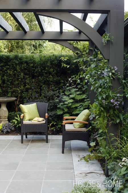 House  Home Outdoor room framed with a black painted arbour overhead, black seating and bluestone floor.
