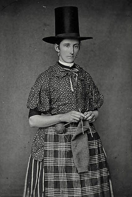 Welsh ladies. Plaids and flowers - yes! And she's keeping her yarn on the end of her needle?