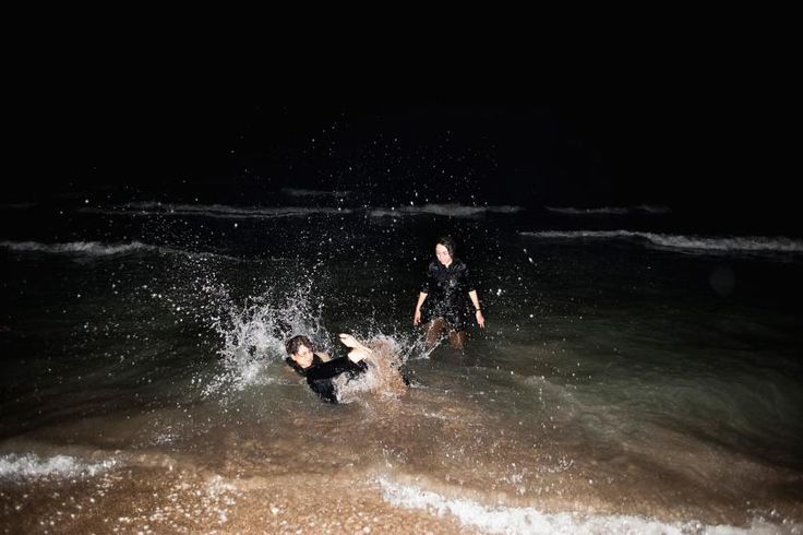 Despite the rules that women are not allowed to swim in public, even fully clothed, Sheida and Behnoosh escape the hot and humid night and hit the Caspian Sea with their manteaus and scarves on. They were kicked out of the beach for breaking the rules by the guards shortly after. Mazandaran, Iran, July 14, 2010.