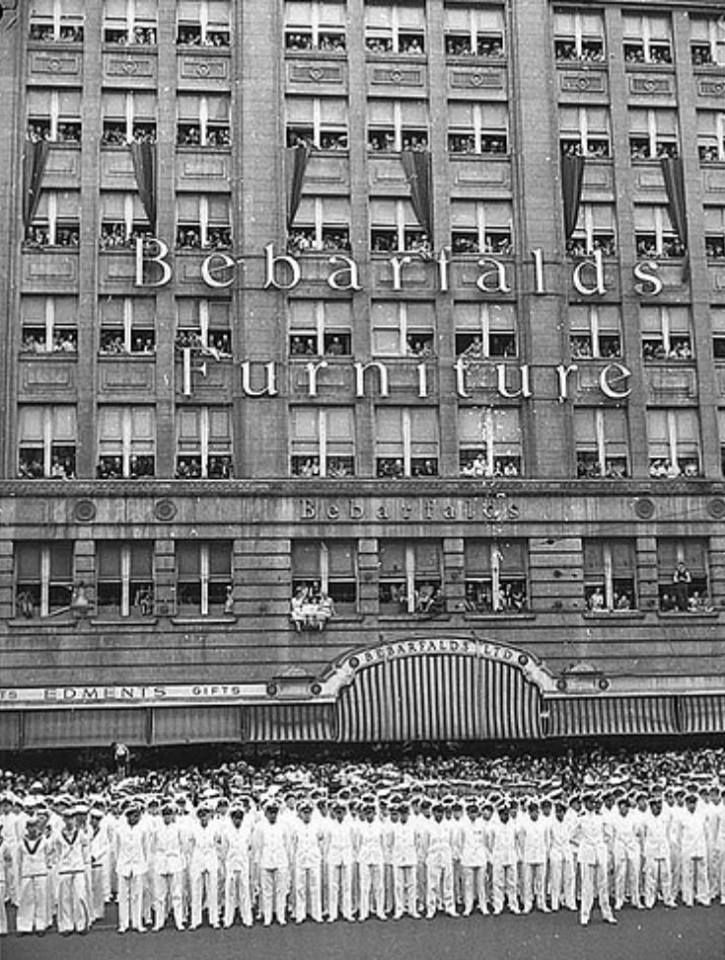 Bebarfald's Building, George St, Sydney, 11 February 1941. Men of the HMAS Sydney parade opposite the Sydney Town Hall for a presentation honouring the crew for their role in the sinking of the Italian cruiser Bartolomeo Colleoni in 1940. 9 months later many of these men perished when the HMAS Sydney was sunk in action against the German raider Kormoran. State Library of NSW
