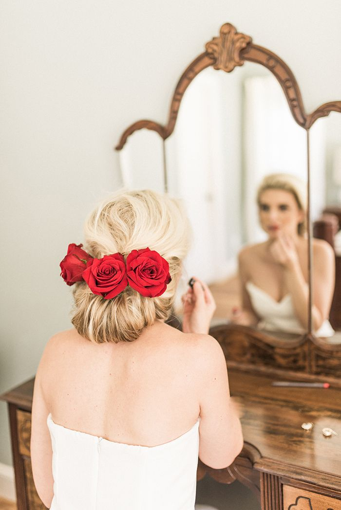 Elegant Chignon Hairstyle with Red Roses for a Winter Bride  https://heyweddinglady.com/warm-winter-wedding-colors-timeless-style/    #wedding#weddinginspiration#weddingcolors#winterwedding#vintagewedding#weddingeditorial#styledshoot #brides #weddinghair #hairstyle
