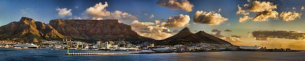 Panoramic view of the Cape Town South Africa city skyline at sunset. Table Mountain, the soccer stadium and the cruise ship Queen Mary are in the foreground. This colorful and dramatic image will enhance an office reception or boardroom and a home living room or rec room.