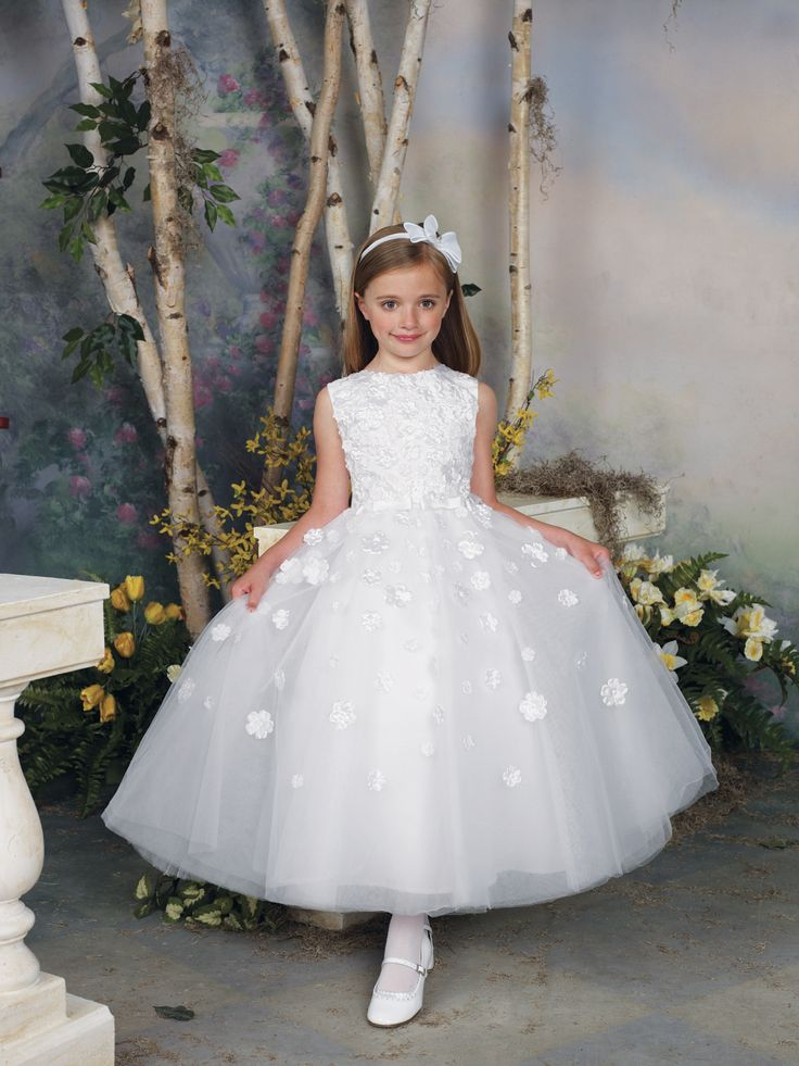 Sleeveless tulle, satin and taffeta tea-length A-line dress with jewel neckline, bodice covered with three-dimensional multi-size taffeta flowers, satin bows accent waistline, full tulle semi-circular skirt features matching scattered flowers. Sizes:2 – 16