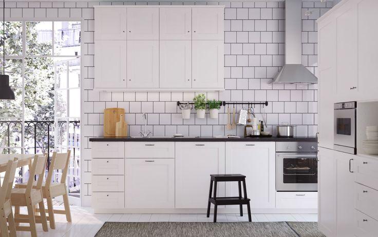 ホワイトの普通サイズのキッチンにブラックのワークトップ、取っ手、ノブ。ステンレス製のレンジフードとオーブン、電子レンジも備えている。
