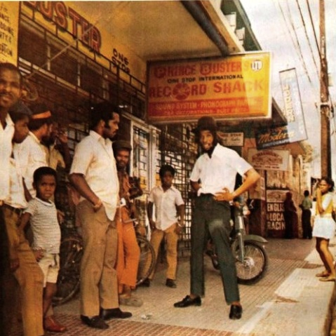 PRINCE BUSTER'S RECORD SHACK in Kingston, Jamaica: record store and headquarter of Voice Of The People record company. Here in 1972 with owner/singer/emcee/producer PRINCE BUSTER and legendary emcee BIG YOUTH.