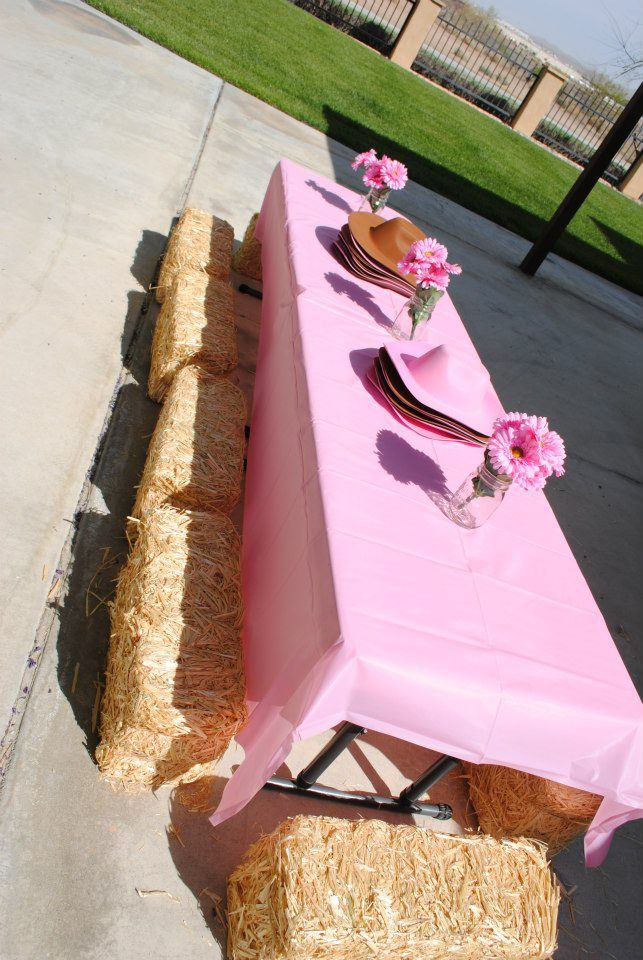 Simple but beautiful party table setup - Solid colored pink tablecloth, cowboy hat accents, pink flowers and the most creative part hay stacks as seats.