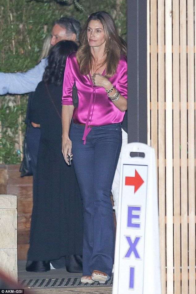 The sidewalk is her catwalk! Donning a vibrant silk magenta blouse and flares, the 50-year...