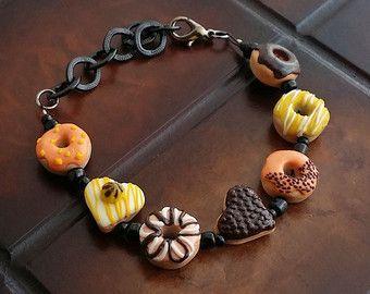 Cookie hart gedoopt In chocolade armband - Bisquit bedelarmband uit polymeerklei - miniatuur Cookie / Biscuit sieraden - chocolade hart  Cookie hart gedoopt in chocolade armband handgemaakt uit polymeerklei. Armband bestaat uit 5 cookies in hart vorm (gedoopt in chocolade), 6 polymeer klei donker bruine kralen en een knevel gesp. Een lief en leuk armband die een prachtige gift keuze zou maken!  Grootte: Cookie hart bedels zijn 1 tot 1,5 cm. armband is 19 cm lang.  Variatie: Als u een…