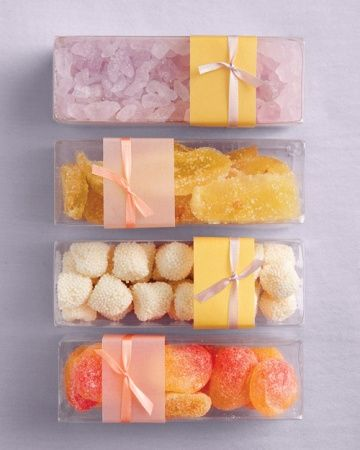 A Variety of Candies Wrapped in Boxes  A variety of colorful candy in clear rectangular boxes, wrapped with translucent paper, makes for stylish favors. Acetate boxes (T109), Glerup Revere Packaging, glerup.com. 3  1/2mm ribbon (ER1540), Mokuba New York. Translucent paper, Paper Presentation. Lavender rock candy, crystallized ginger, and champagne gumdrops, all The Sweet Life. Gummi peaches (C100857), Haribo, Candy Warehouse