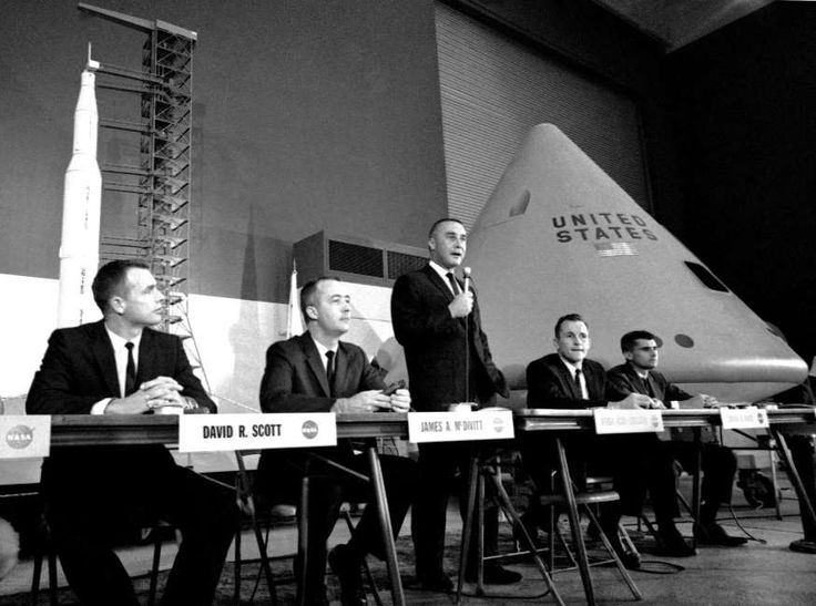 In this Aug. 4, 1966 file photo, command pilot Virgil Grissom speaks during a news conference in Downey, Calif., with a mock-up of the Apollo spacecraft at right. Grissom's crewmen are Roger B. Chaffee, right, and Edward H. White, second from right.