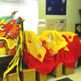 This is the dragon I made for my sixth graders Holiday concert!!  All it took was cardboard boxes underneath, a dragon face from oriental trading,red material about 19 yards, and gold plastic tablecloths. You can also add streamers and Chinese decor! Budget- $100.00