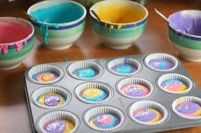 Use a white cake mix and divide into four bowls; add food coloring to each bowl and spoon a little of each into the cupcake holders! So neat!