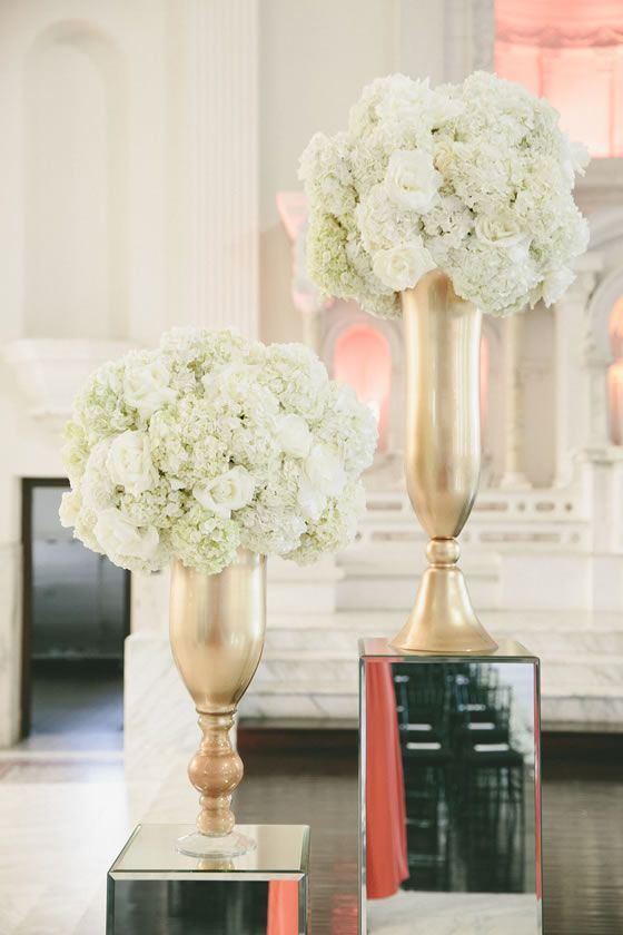 Voluminous white floral arrangements in gold urns sit atop mirrored columns. Talk about a wedding fashion statement! Bob Gail Special Events. Onelove Photography.